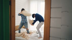 El hombre joven emocionado y la mujer se están divirtiendo en casa que luchan las almohadas y que ríen después el abrazo y besars almacen de video