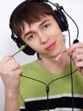 El hombre joven en auriculares con los alambres Foto de archivo