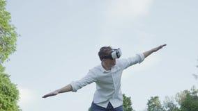 El hombre joven en auriculares de la realidad virtual se separó los brazos al lado, imitando el vuelo de un aeroplano en el parqu almacen de metraje de vídeo