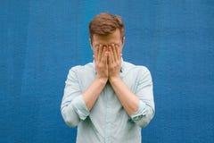 El hombre joven en camisa azul se cierra la cara en la tensión y la depresión Imagen de archivo libre de regalías