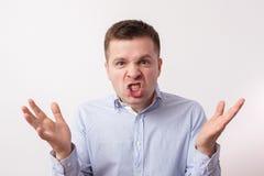 El hombre joven en camisa en cólera grita y amenaza Imagen de archivo libre de regalías