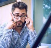 El hombre joven en camisa de tela escocesa y lentes tiene conversación telefónica, sentándose en el café imagen de archivo