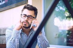 El hombre joven en camisa de tela escocesa y lentes tiene conversación telefónica, sentándose en el café fotografía de archivo
