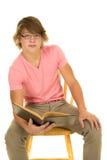 El hombre joven en camisa rosada sienta la mirada abierta del libro Imagen de archivo libre de regalías