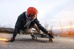 El hombre joven en casco va a resbalar, resbalar con las chispas en un longboard en el asfalto Foto de archivo