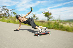 El hombre joven en casco va a resbalar, resbalar con las chispas en un longboard en el asfalto foto de archivo libre de regalías