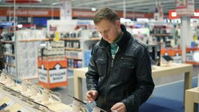 El hombre joven en chaqueta de cuero negra está eligiendo un nuevo teléfono móvil en una tienda, comprobando cómo trabaja metrajes