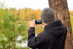 El hombre joven en chaqueta negra y sombrero hecho punto gris está tomando una foto del paisaje del otoño en el teléfono móvil en fotos de archivo libres de regalías
