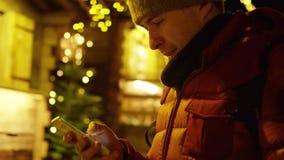 El hombre joven en chaqueta roja utiliza su smartphone en la tarde contra la iluminación de la Navidad Tirado en c almacen de video