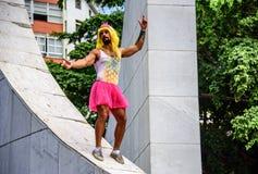 El hombre joven en corona rosada, la peluca amarilla, el leotardo con la piña y el tutú rosado brillante bordean la situación en  Fotos de archivo libres de regalías