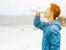 El hombre joven en deporte viste el agua potable después de entrenamiento en la playa Imagen de archivo