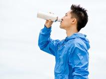 El hombre joven en deporte viste el agua potable después de entrenamiento en la playa Fotos de archivo