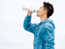 El hombre joven en deporte viste el agua potable después de entrenamiento en la playa Fotografía de archivo