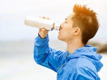 El hombre joven en deporte viste el agua potable después de entrenamiento en la playa Foto de archivo