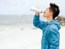El hombre joven en deporte viste el agua potable después de entrenamiento en la playa Imágenes de archivo libres de regalías