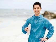 El hombre joven en deporte viste el agua potable después de entrenamiento en la playa Imagenes de archivo