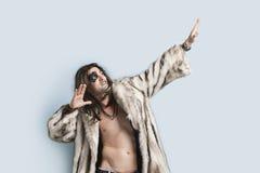 El hombre joven en el abrigo de pieles que miraba para arriba con los brazos aumentó contra fondo azul claro Fotografía de archivo