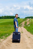 El hombre joven en el camino en campo con una maleta Foto de archivo
