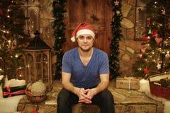 El hombre joven en el casquillo de Santa Claus se sienta en casa en pasos del estilo adornado de la Navidad Imagen de archivo