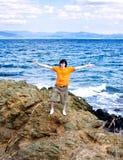 El hombre joven en el mar en una piedra Fotos de archivo libres de regalías