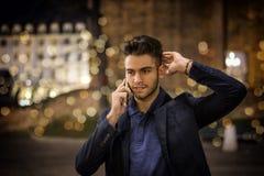 El hombre joven en el teléfono en la noche con la ciudad se enciende Foto de archivo