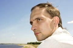 El hombre joven en el verano en la batería de río Imagenes de archivo