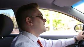 El hombre joven en gafas de sol está conduciendo un coche moderno almacen de metraje de vídeo