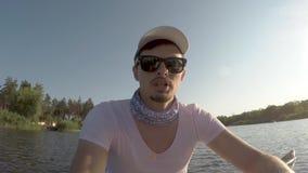 El hombre joven en gafas de sol se sienta en kajak en el fondo del río almacen de video