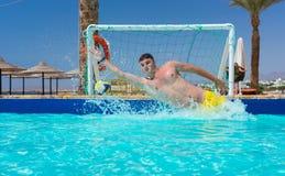 El hombre joven en la acción salta la meta en la piscina que juega water polo Fotos de archivo
