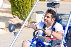 El hombre joven en la rueda del cochecillo muestra la mano a un lado Foto de archivo libre de regalías