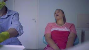 El hombre joven en máscara médica trata los dientes a su paciente femenino La mujer que visita el tratamiento de Dental del denti almacen de video