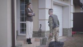 El hombre joven en militares se cierra con el bolso grande se vuelve a casa y encuentra a su esposa delante de la casa La señora  almacen de video