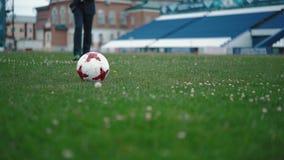 El hombre joven en pantalones, corre al campo de fútbol y golpea la bola, primer almacen de metraje de vídeo