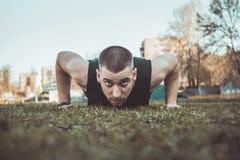 El hombre joven en ropa de deportes hace ejercicios en la hierba en el estadio entrenamiento en la tierra prensa-para arriba Pect fotografía de archivo libre de regalías
