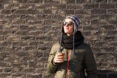 El hombre joven en ropa del invierno sostiene la taza de café Foto de archivo