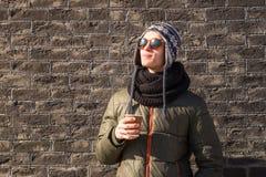 El hombre joven en ropa del invierno sostiene la taza de café Fotos de archivo libres de regalías
