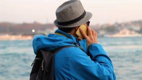 El hombre joven en sombrero habla por el teléfono en la playa almacen de metraje de vídeo