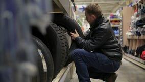 El hombre joven en el supermercado que elige el automóvil pone un neumático la situación en los estantes almacen de metraje de vídeo