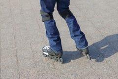 El hombre joven en tejanos patina sobre ruedas Foto de archivo libre de regalías
