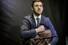 El hombre joven en traje de negocios azul marino se sienta con la maleta Imágenes de archivo libres de regalías