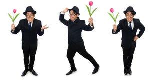 El hombre joven en traje negro con la flor aislada en blanco imagen de archivo libre de regalías