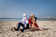 El hombre joven en traje se sienta con la mujer de moda en la playa Imágenes de archivo libres de regalías