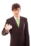 el hombre joven en traje y lazo rayados demuestra la tarjeta personal Imagen de archivo