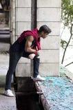 El hombre joven en un edificio viejo mira hacia fuera la ventana Fotos de archivo