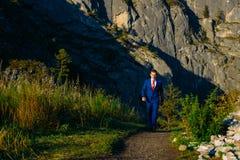 El hombre joven en un traje de negocios con el lazo rojo en el fondo de monta?as va a su objetivo en un d?a de verano soleado imagen de archivo libre de regalías