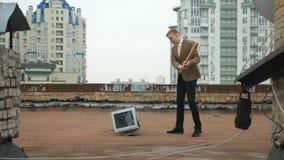 El hombre joven en un traje rompe un monitor con un palo en el tejado Palo, violencia, odio, anarquía, destrucción 60 fps almacen de metraje de vídeo