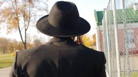 El hombre joven en un traje y un sombrero elegantes negros va y habla en el teléfono, primer, cámara lenta metrajes