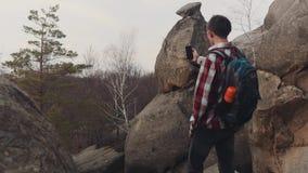El hombre joven en una camisa a cuadros se coloca en el top de la roca grande y toma varios tiros del paisaje asombroso Ningunas  almacen de metraje de vídeo