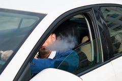 El hombre joven en una chaqueta azul fuma un cigarrillo electrónico mientras que conduce un coche Foto de archivo