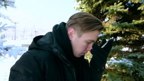 El hombre joven en una chaqueta caliente y guantes controla el teléfono del tacto con su nariz y contesta a la llamada El concept almacen de metraje de vídeo